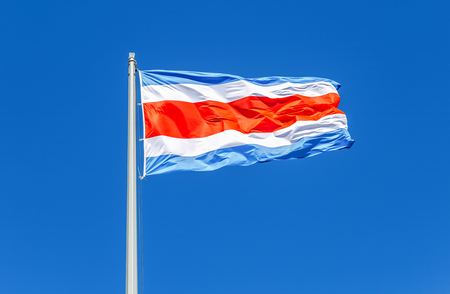 National flag of Costa Rica waving and blowing in the wind against the blue sky
