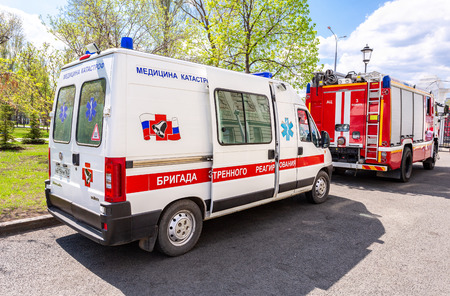 Samara, Russia - May 9, 2018: Ambulance car and fire truck parked up at the street. Text on russian: