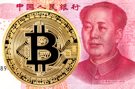 Cryptocurrency Bitcoin lying on the Chinese 100 yuan banknote. Business concept of new virtual money Stock Photo