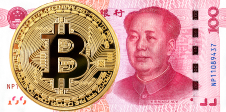 Cryptocurrency Bitcoin lying on the Chinese 100 yuan banknote. Business concept of new virtual money Фото со стока