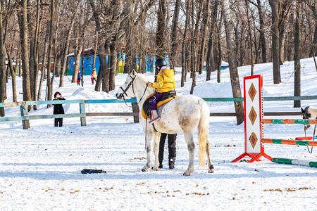 Samara, Russia - February 10, 2018: Children learn to ride horses in winter park