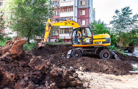 Samara, Russia - May 25, 2017: Yellow excavator digging a trench near the apartment building in summer sunny day Редакционное