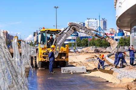 Saint Petersburg, Russia - August 7, 2018: Workers laying curbstone on a city street in summer sunny day 新聞圖片