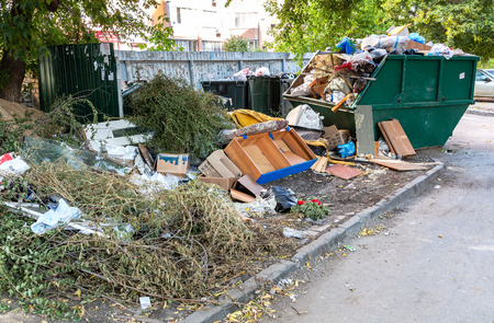 Samara, Russia - September 4, 2018: Containers with garbage and different rubbish at the sunny city street Editorial