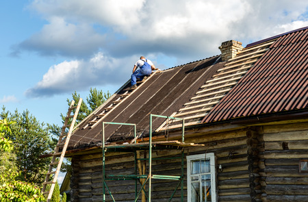 Novgorod, Russia - August 22, 2018: Worker repairs the roof of a wooden house in the village