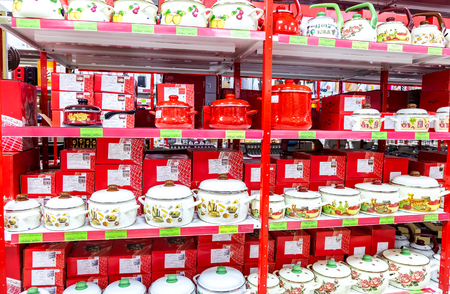 Samara, Russia - March 30, 2019: Different bright metal enamelware, cooking pots containers utensils for sale on store shelf