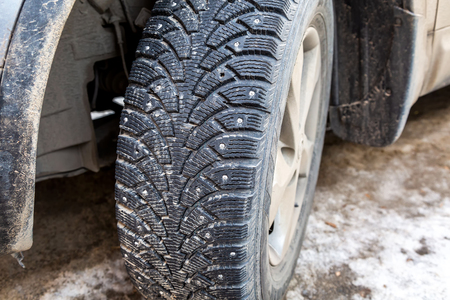 Used winter studded car wheel on the snow Stockfoto