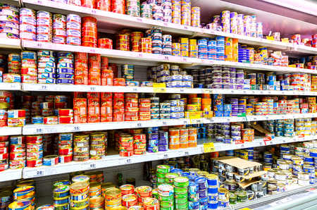 Samara, Russia - March 30, 2019: Various canned fish in cans for sale on the shelves at the chain hypermarket Karusel