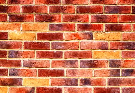 Vintage red brick wall as background texture. Bricks masonry with uneven seams