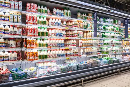Samara, Rusia - 13 de abril de 2019: Varios productos lácteos frescos listos para la venta en la cadena de hipermercados Lenta. Leche envasada como fondo Editorial