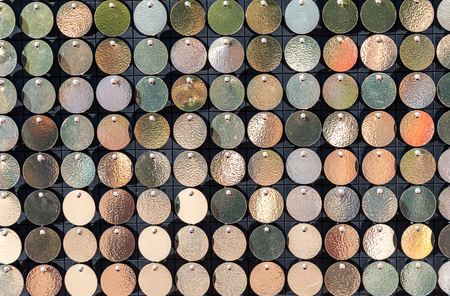 Background from small round metal plates of golden color. Golden background of round gold discs chaotically rotating in wind