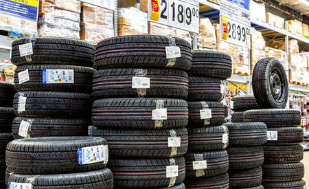 Samara, Russia - May 1, 2018: Summer vehicle tires stacked up for sale in the chain hypermarket. New tyres for sale Redakční