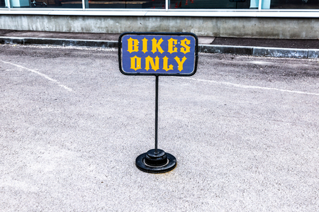 Parking sign for bikes only next the office of official dealer motorcycles