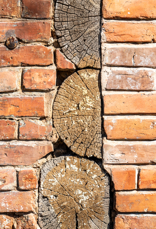 Vintage red brick wall with wooden logs as background Stock Photo