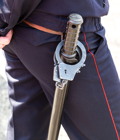 Russian policeman with rubber truncheon and steel handcuffs
