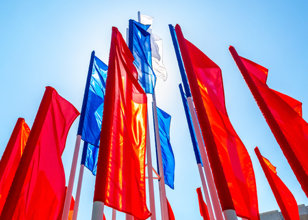 Colorful holiday flags fluttering against the blue sky