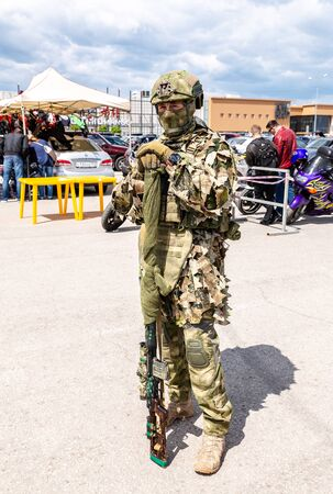 Samara, Russia - May 18, 2019: Unidentified Russian soldier in camouflage army uniform with sniper rifle in hand at the street during the city holiday