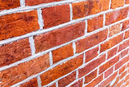 Vintage red brick wall as background texture. Bricks masonry with seams