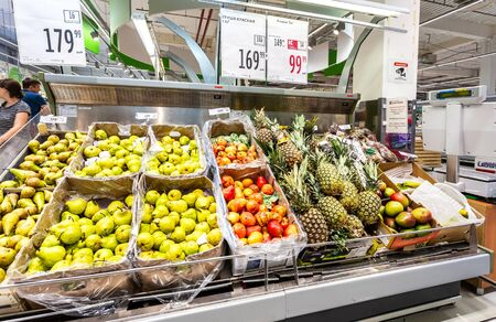 Samara, Russia - June 9, 2019: Fresh pineapples and pears fruits ready for sale in the chain hypermarket