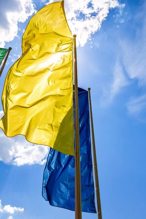 Colorful flags in the wind against the blue sky background