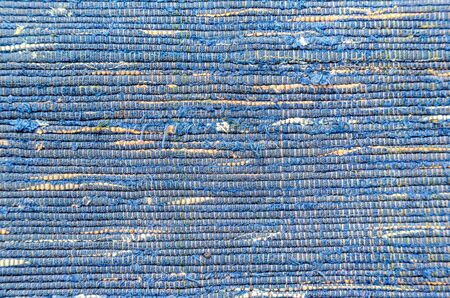 Old homespun doormat made from strips of cloth as background. Texture of a homemade rug from different fabrics