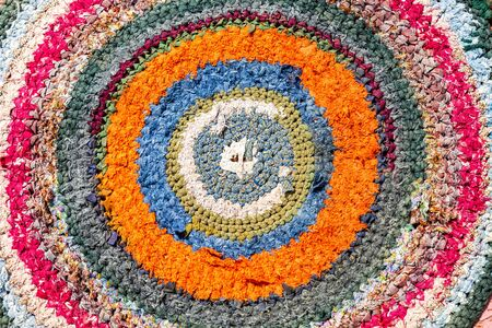 Old handicraft rug made from strips of cloth as background. Texture of a homespun doormat from different fabrics Banco de Imagens