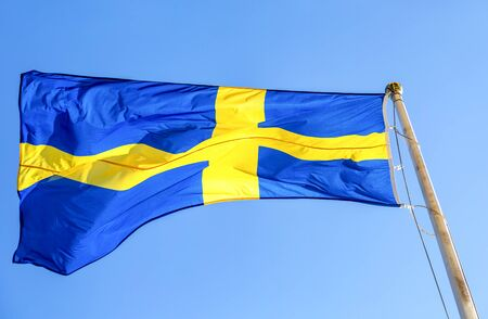 National flag of Sweden flying in the wind against the blue sky Stock Photo