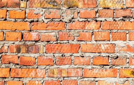 Rough red brick wall as background texture. Bricks masonry with uneven seams Stock fotó