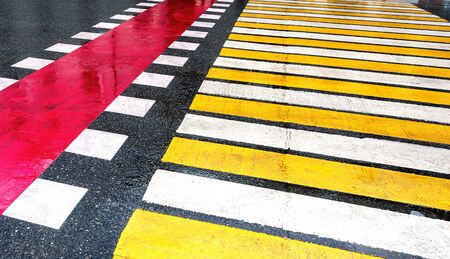 Pedestrian crossing with white and yellow stripes on the asphalt road close up