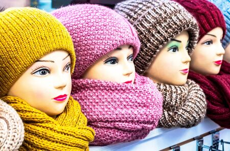 Mannequins female heads in hats and scarfs close up. Woolen knitted caps and scarves. Female headdresses 免版税图像