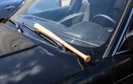 Wooden baseball bat lies on the black car