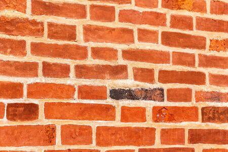 Red brick wall as creative background texture. Bricks masonry with seams