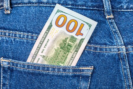 Banknote of one hundred american dollars sticking out of the jeans pocket