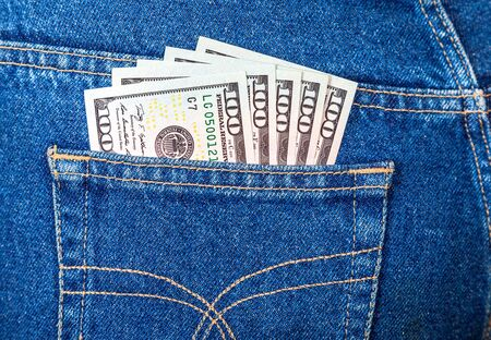 Banknotes of one hundred american dollars sticking out of the jeans pocket