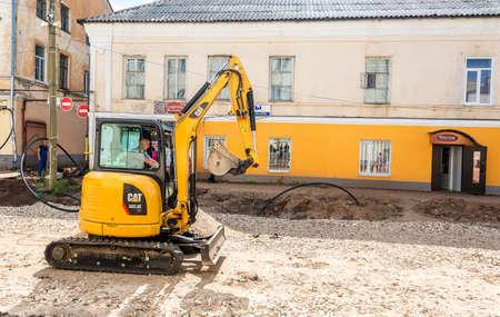 Borovichi, Russland - 22. Juli 2019: Kleiner Bagger, der am Sommertag am Bau einer neuen Straße an der Stadtstraße arbeitet Editorial