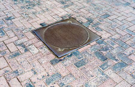 Rusty metal manhole cover on urban pavement road Stock Photo