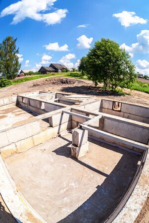 Construction of a new wooden house on the stone foundation. Construction site and house foundation in preparation process in summertime Stock Photo