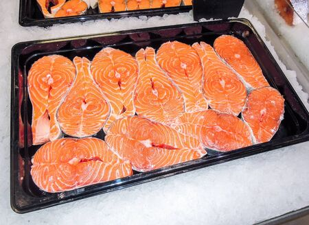 Steaks of fresh salmon on the counter. Raw red fish for sale. Seafood shop