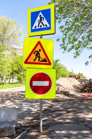 Road signs at the construction site of replacement underground communications in summer day Stock Photo