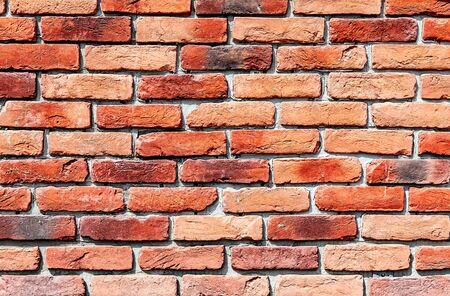 Old weathered red brick wall as background. Bricks masonry with seams. Red brick wall texture