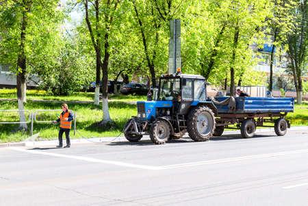 Samara, Russia - May 14, 2020: Road works on painting curbstone fenced on the asphalt road
