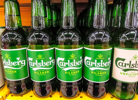 Samara, Russia - March 18, 2020: Carlsberg alcoholic beer ready for sale on the shelf in superstore. Various bottled alcoholic beverages and spirit drinks Editorial