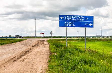 Kazan, Russia - June 10, 2018: Directional sign at a highway roadside to the Kazan in summer. Text in Russian: Kazan, Sorochy Mountains