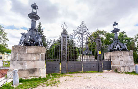 Moscow, Russia - July 10, 2019: Entrance with metall gate and statues of griffins to the manor court of estate of Vlakhernskoye - Kuzminki. Installed in 1830