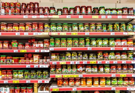 Samara, Russia - May 3, 2019: Canned vegetables in glass cans on the shelves in a grocery store. Food background