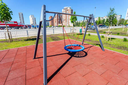 Samara, Russia - May 29, 2020: Children's playground for kids in new district with swing for play and rest. Recreation site with swing in city