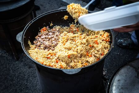 Cooking appetizing traditional oriental pilaf with meat in a large cauldron outdoors