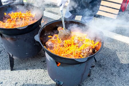 Cooking appetizing traditional food in a large cauldrons outdoors during the ethnic holiday
