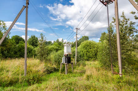 Old voltage power transformer substation at the russian village. Distribution of electricity. Electrical energy Stock Photo
