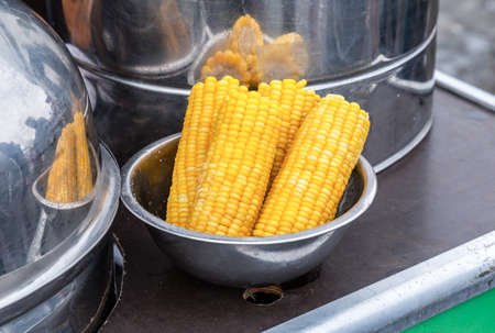 Steamed corn in a cooking saucepan, street food. Boiled corn cobs with a bit of sugar or salt to get a delicious taste Stock Photo